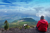 Western tourist is sitting at the crater of Nyiragongo Volcano