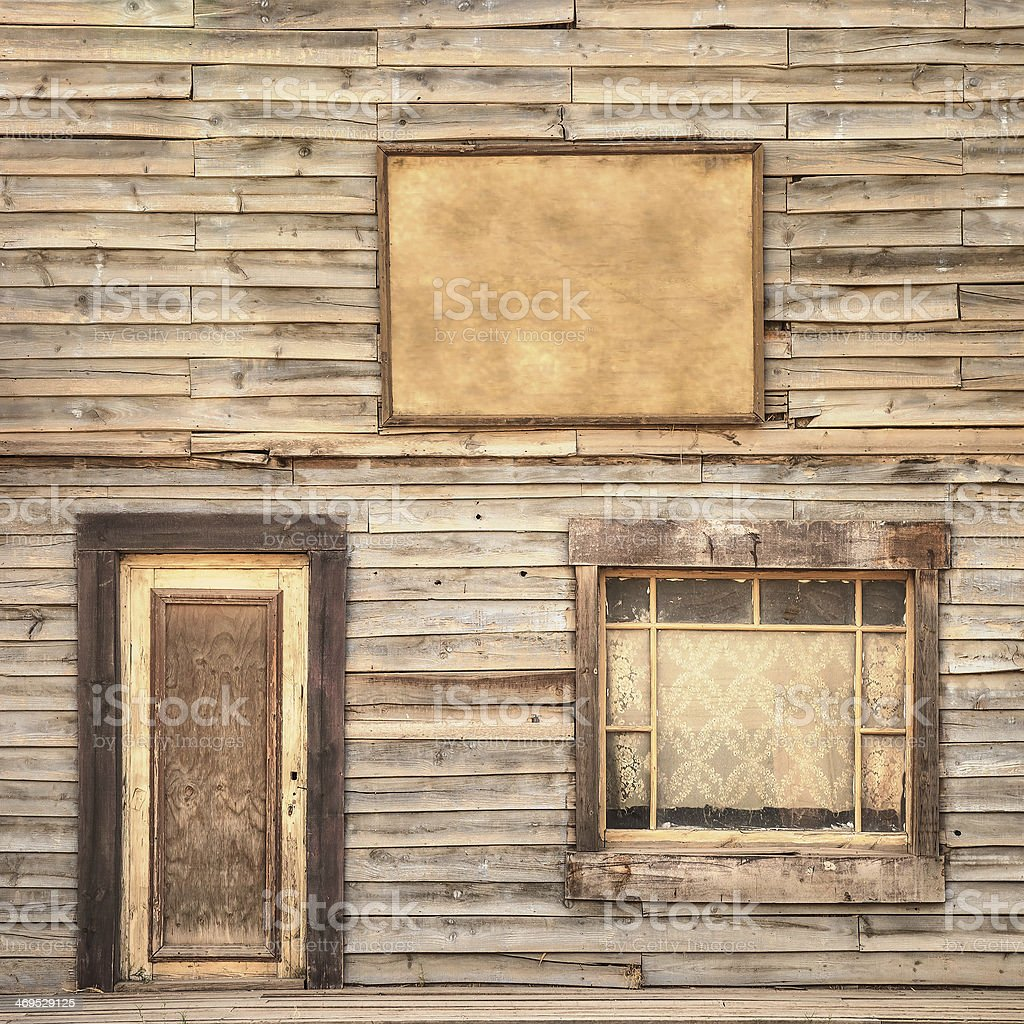 Western vintage wooden facade background. Door, window and blank board stock photo