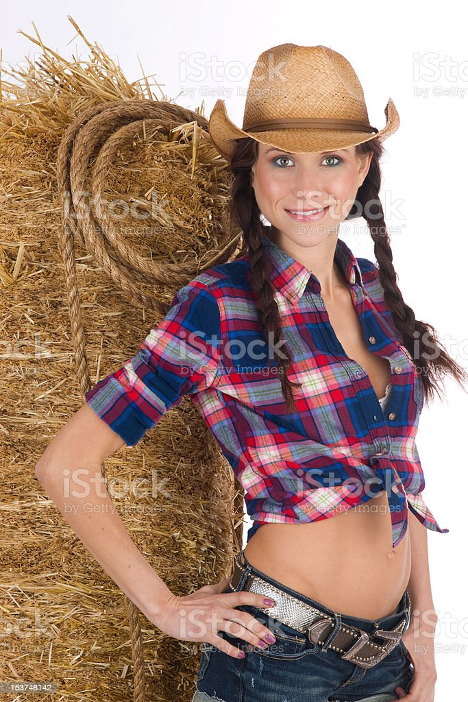 Western Woman Cowgirl Standing Leaning Against Straw Hay Bale royalty-free stock photo