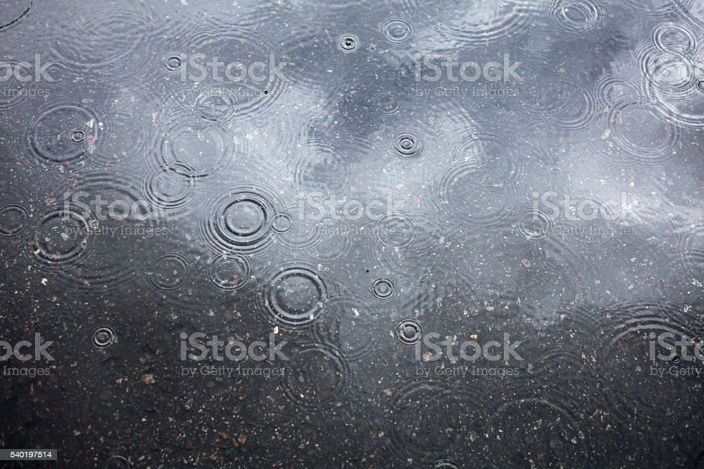 Wet asphalt, puddle and raindrops stock photo