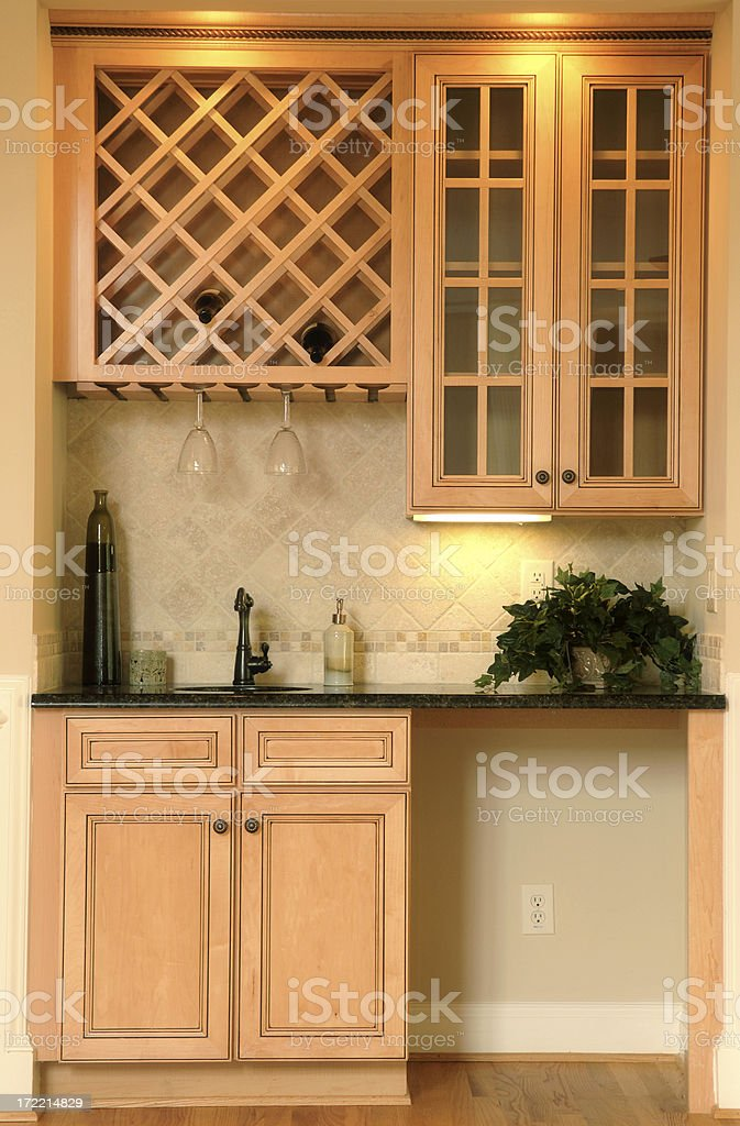 Wet bar of light wood filled sparsely stock photo