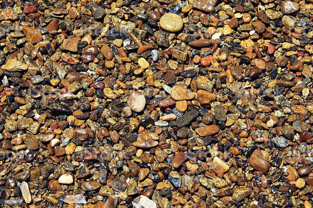 Wet beach pebbles under sunshine stock photo