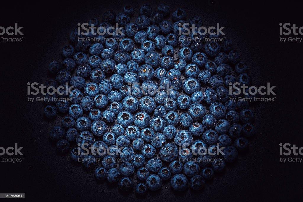 Wet blueberries on black slate stock photo