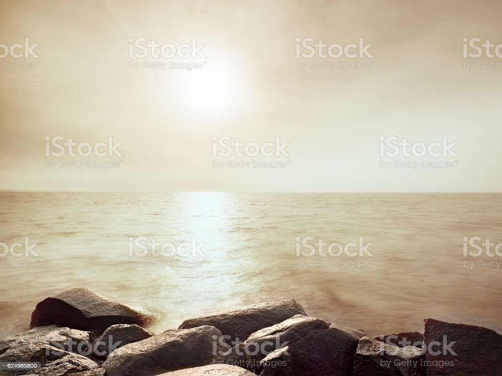 Wet boulders in shore. Stony sea coast defies to waves stock photo