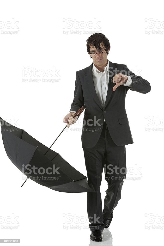 Wet businessman holding umbrella showing thumbs down sign royalty-free stock photo