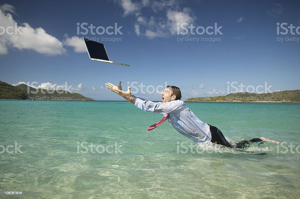 Wet Businessman Splashing in Sea with Laptop royalty-free stock photo