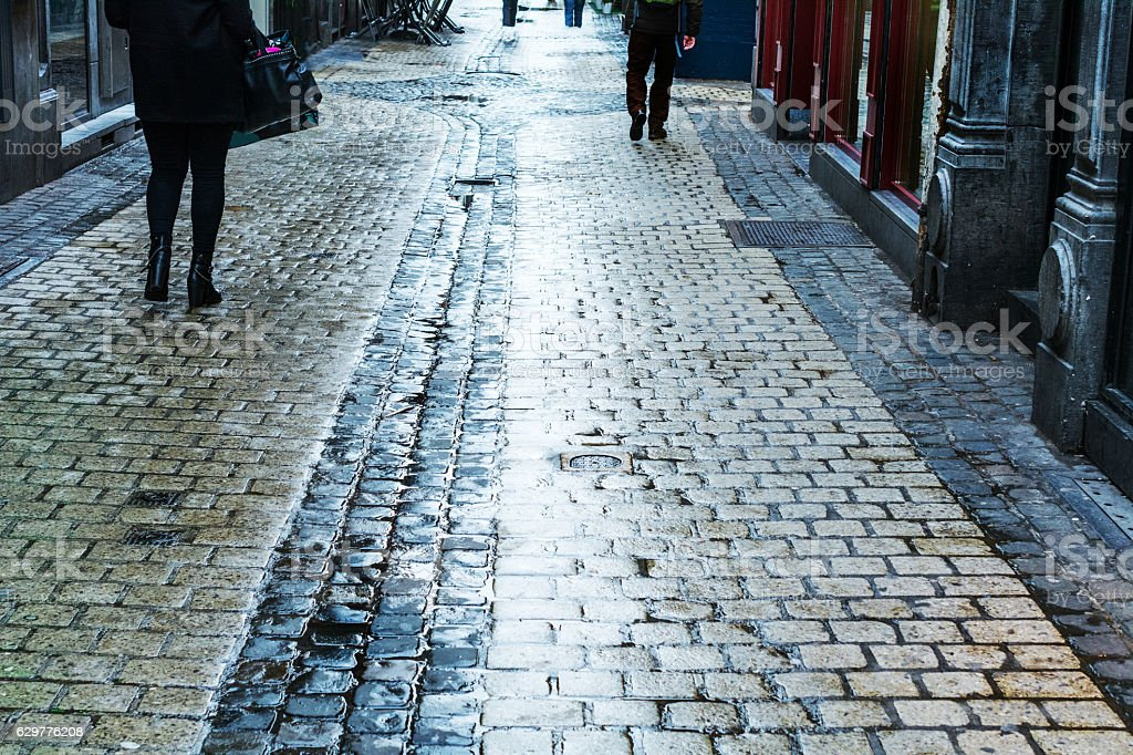 Wet classic shopping street with wet reflective cobble stones stock photo