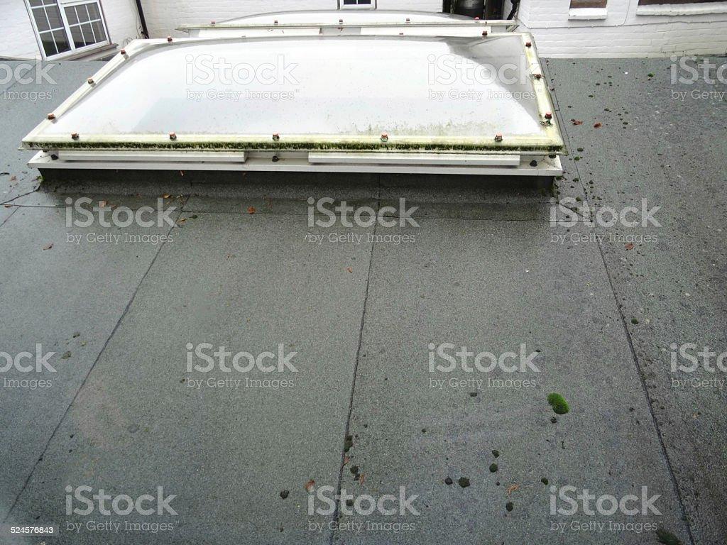 Wet felt / asphalt flat roof, bowed skylights / rooflight windows image stock photo