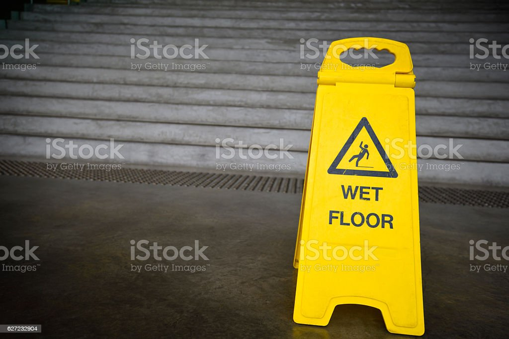 Wet floor sign next to stairs (in station building) stock photo
