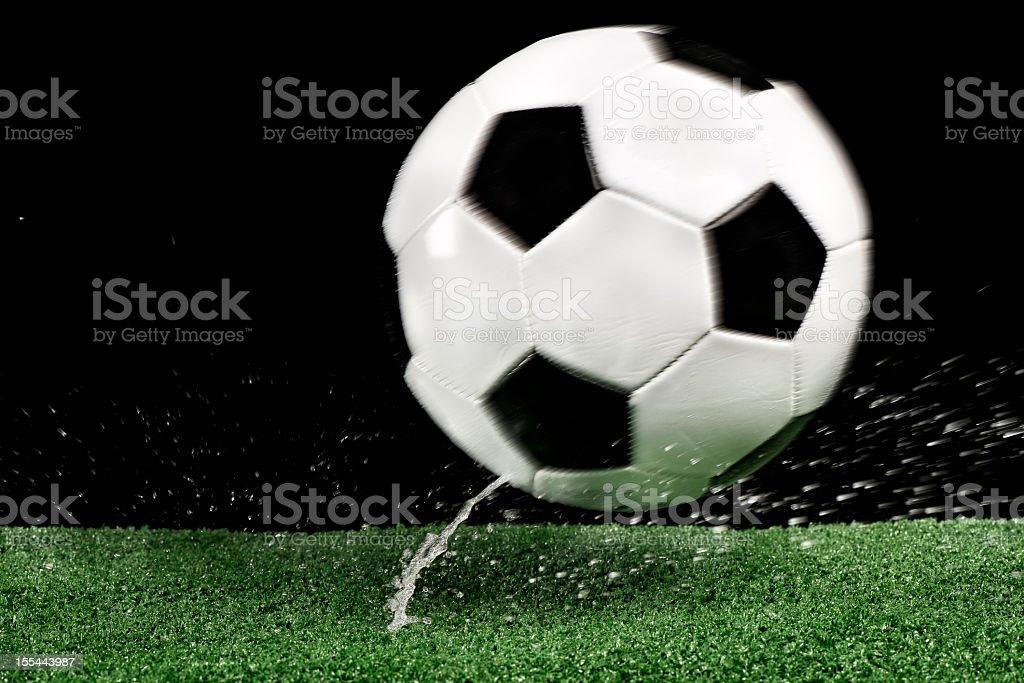 Wet football bouncing on green artificial grass stock photo