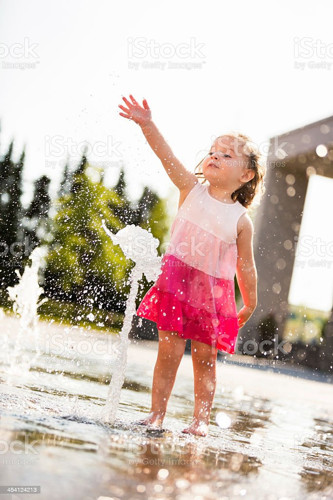 Wet girl playing with water from fountain royalty-free stock photo