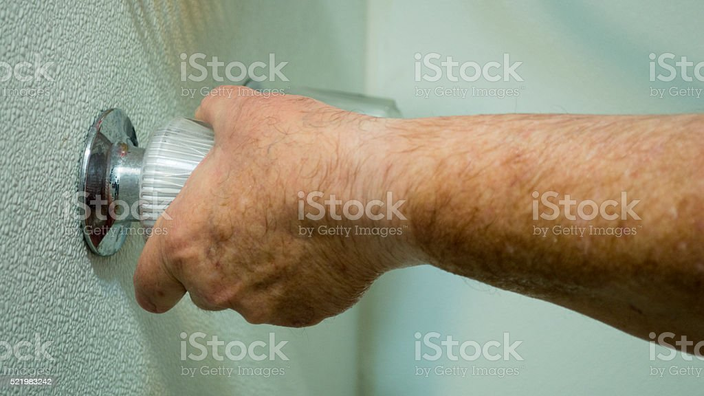 Wet hand conserving water in shower stock photo