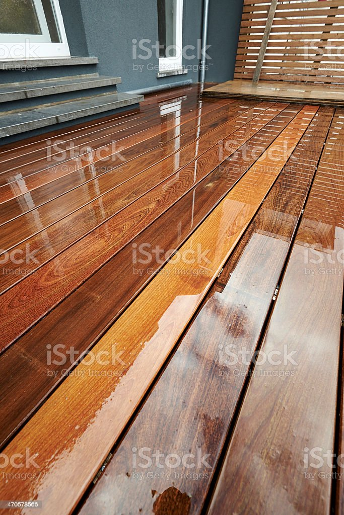 Wet Outdoor Wood Surface in front of a renovated wall stock photo