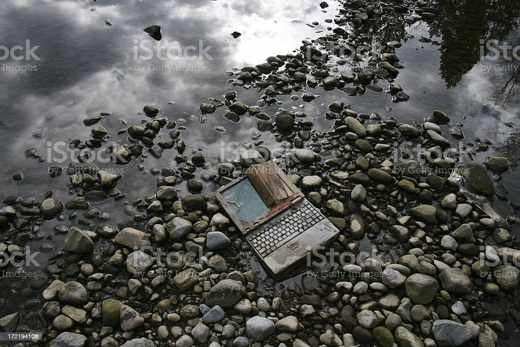 Wet Rusty laptop lying on river rocks royalty-free stock photo