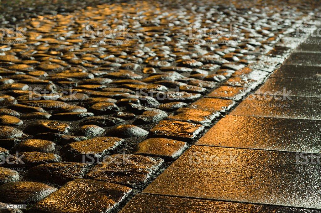 Wet shiny block pavement at night stock photo
