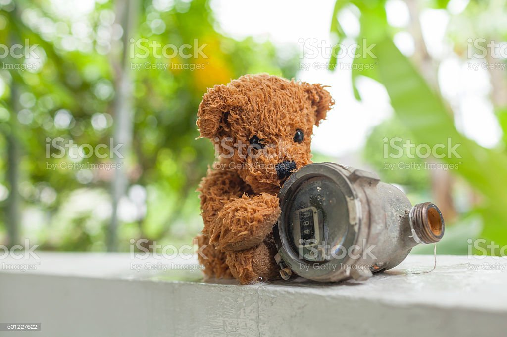 Wet Teddy bear and old water meter stock photo
