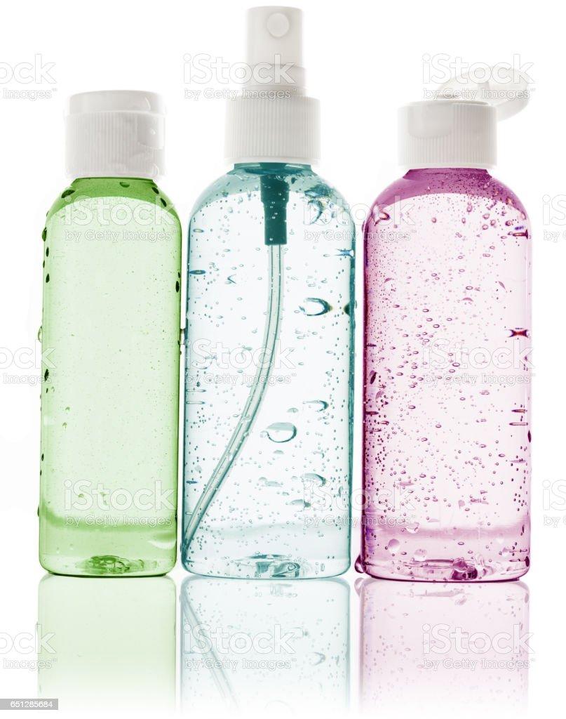 wet toiletry bottles on white background stock photo