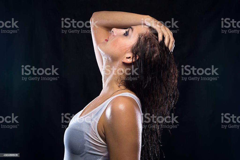 Wet woman in white t-shirt looking up stock photo