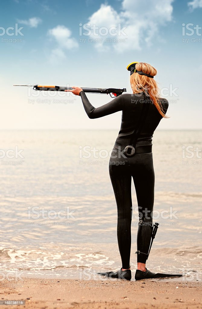 Wetsuit woman hold speargun stock photo