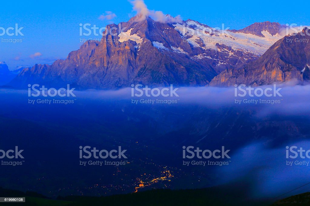 Wetterhorn above illuminated Grindelwald at evening, Swiss Alps stock photo
