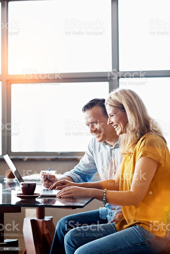 Shot of a mature couple sitting at their dining room table doing...