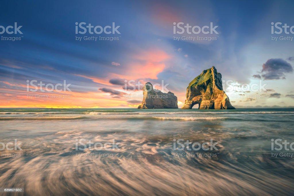 Wharariki beach, New zealand at sunset scenery stock photo