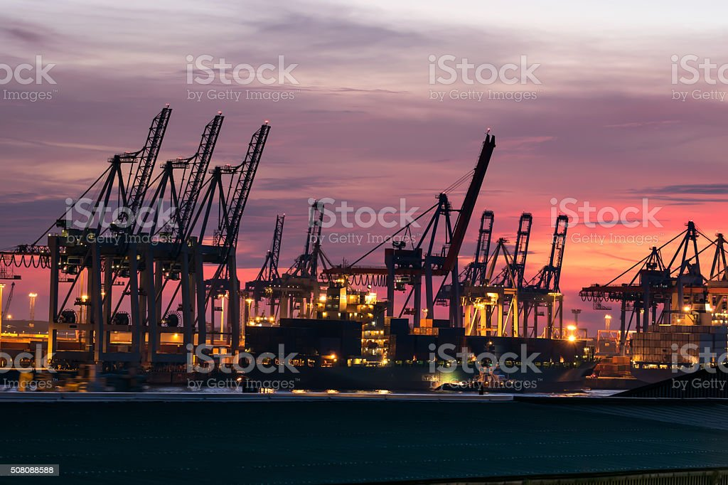 wharf with container ship in red evening mood stock photo