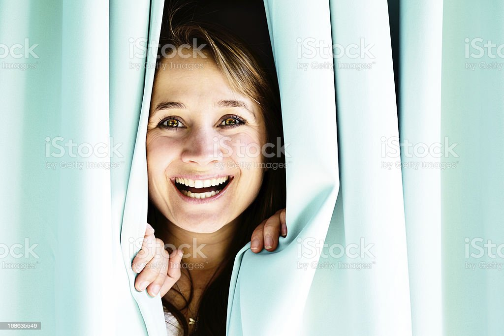 What a lovely surprise! Happy blonde looking through curtains royalty-free stock photo