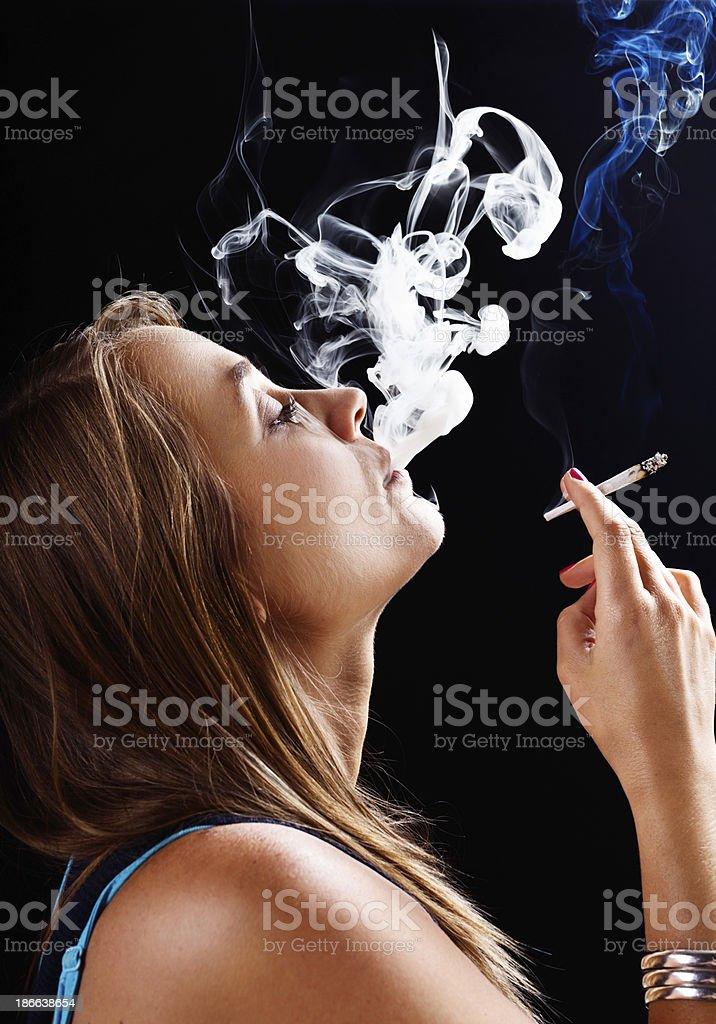 What a rush! Beautiful blonde smoking marijuana stock photo