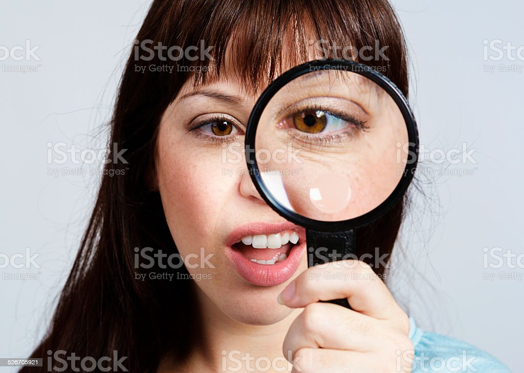 What is that? Young woman looks through magnifying glass unhappily. stock photo