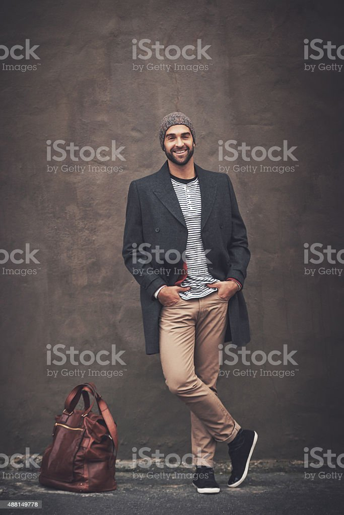 Full length shot of a fashionable young man standing against a dark...