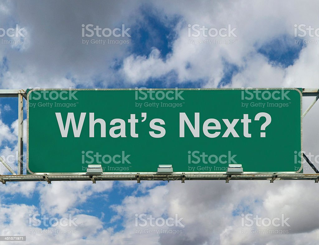 What's Next? written on a green highway sign and clouds stock photo