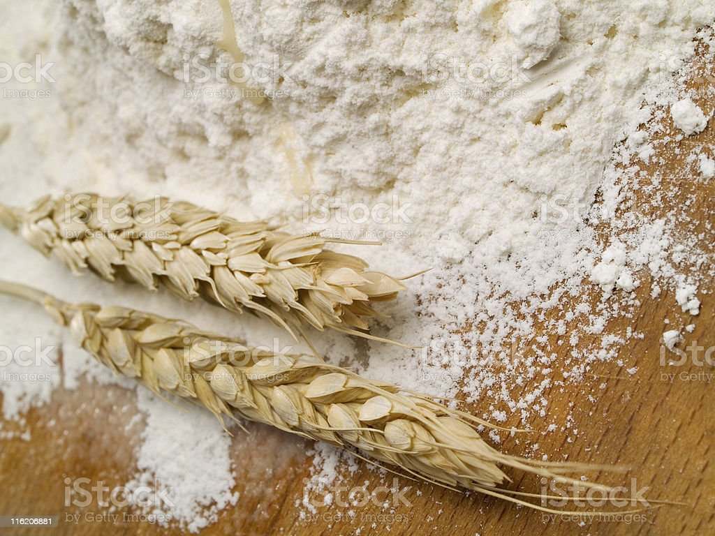 Wheat and flour on a wooden surface stock photo