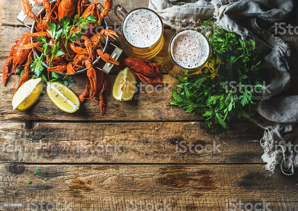 Wheat beer and boiled crayfish over old wooden rustic background stock photo