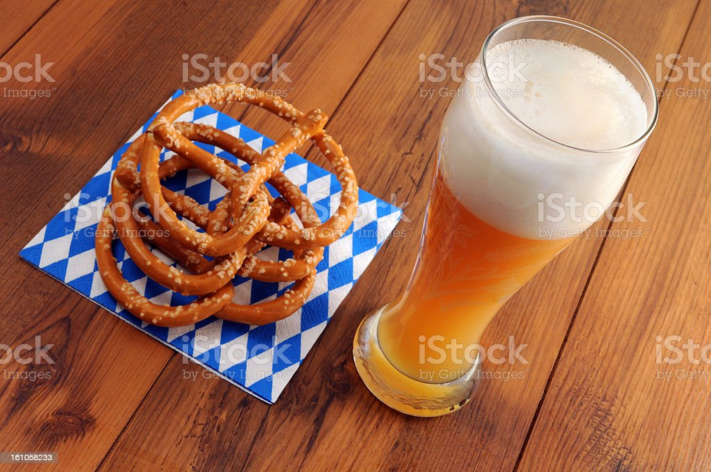 wheat beer and Pretzel on blue white bavarian napkin royalty-free stock photo