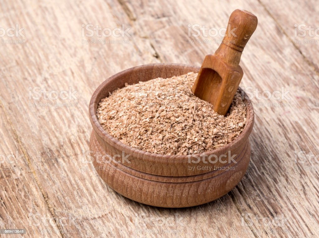 wheat bran in a small wooden bowl stock photo