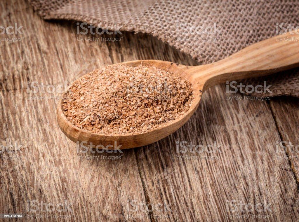 Wheat bran in wooden spoon stock photo