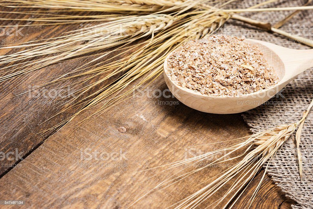 Wheat bran in wooden spoon with wheat ears stock photo