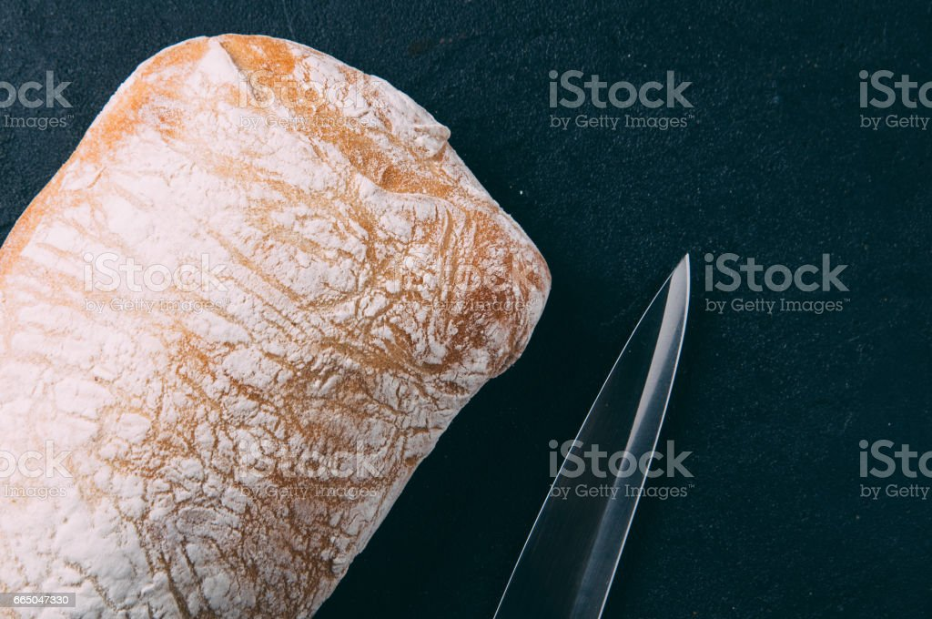 Wheat bread and knife on dark background stock photo