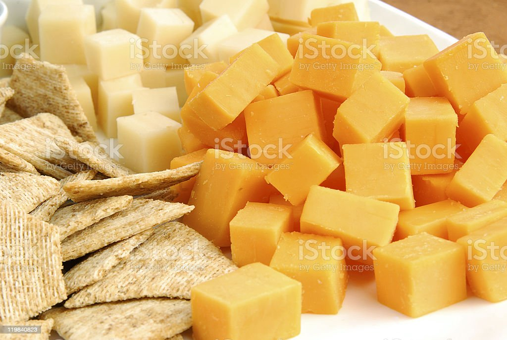 Wheat crackers and cubed cheddar and white cheese stock photo