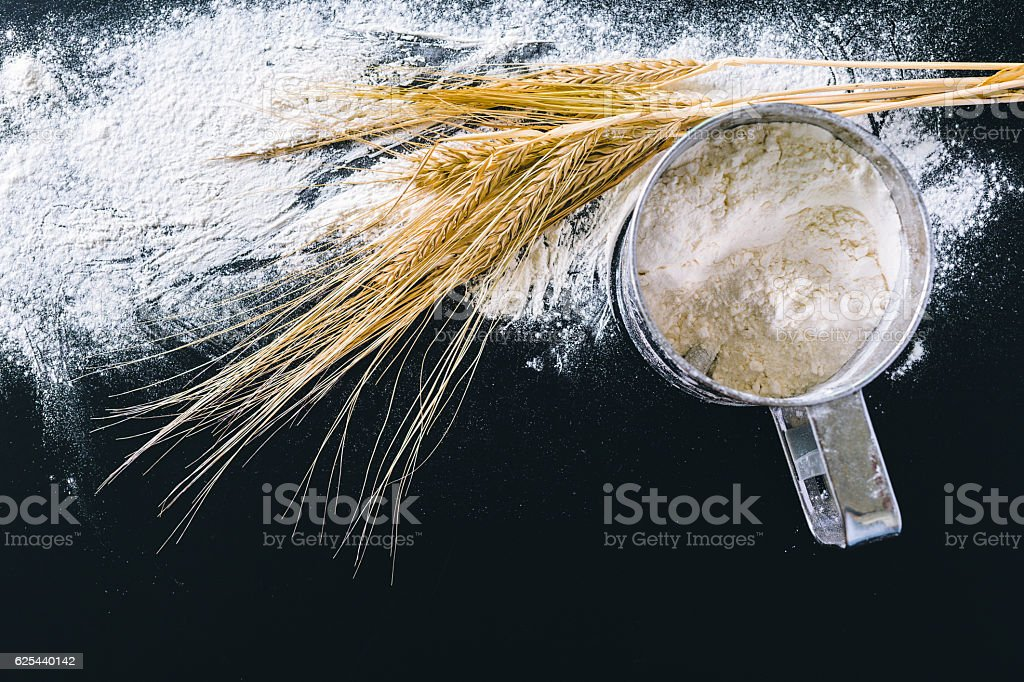 Wheat ears and flour on black background stock photo