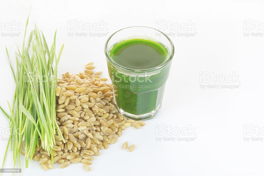 Wheat grass juice on white background stock photo