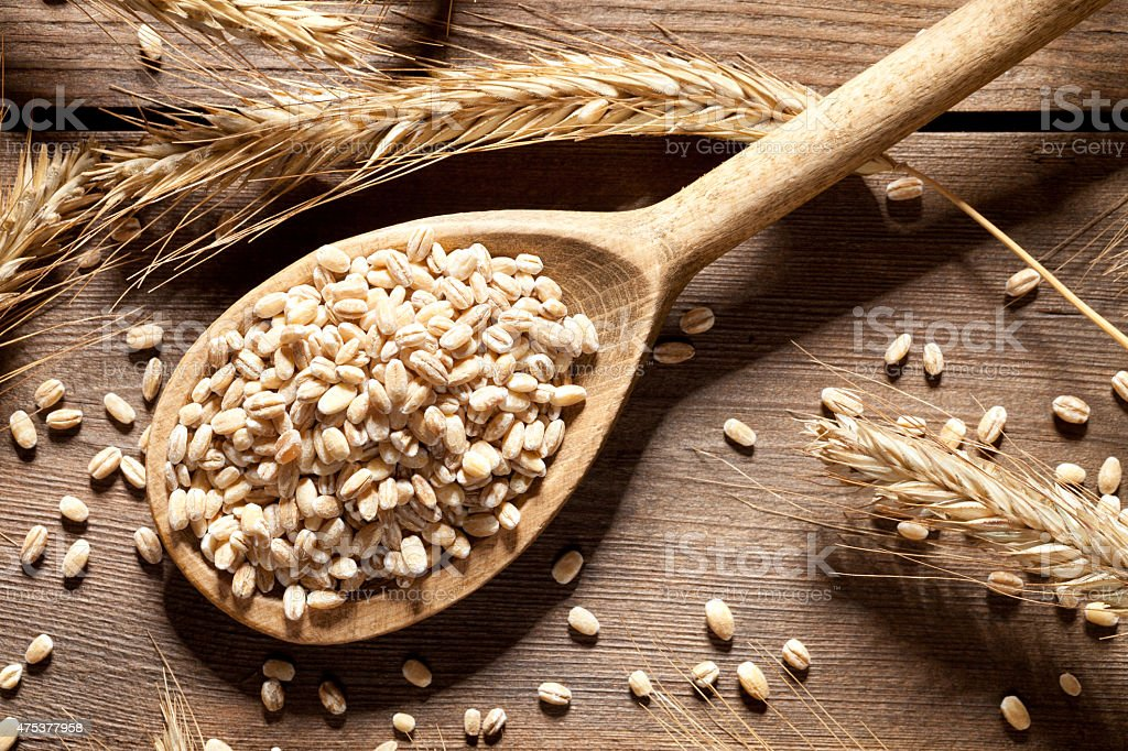 Wheat seed in spoon on old wooden table stock photo