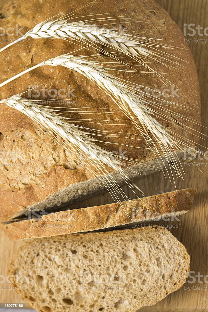 Wheat sliced bread on wood cutting board. Top view royalty-free stock photo