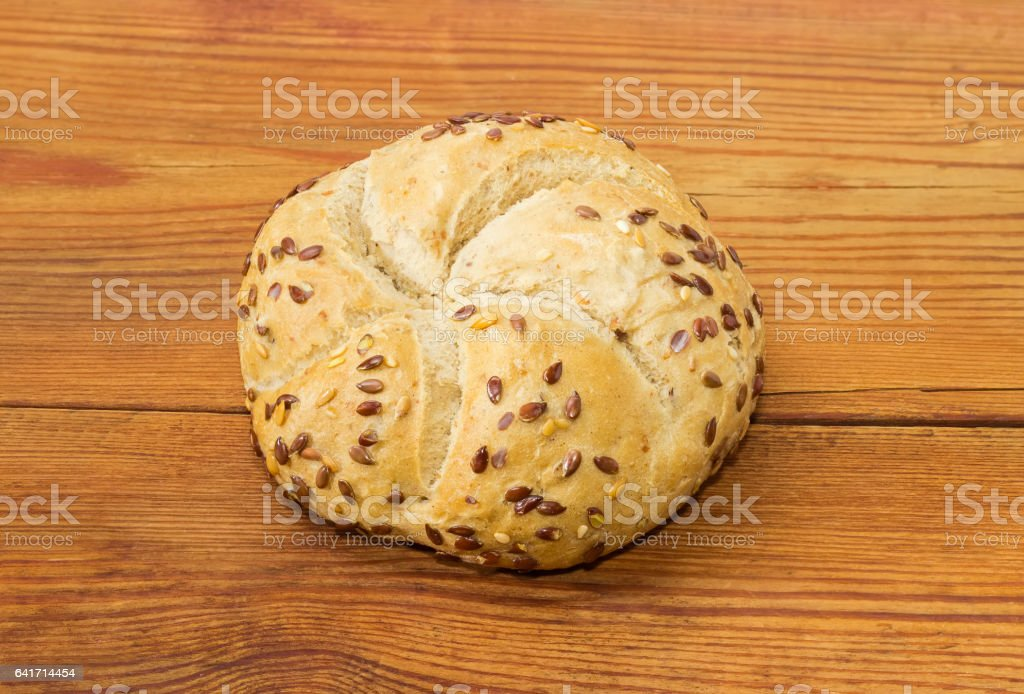 Wheat sourdough bun sprinkled with flax and sesame seeds stock photo