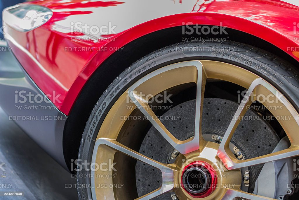 Wheel and front end of a red sports car stock photo