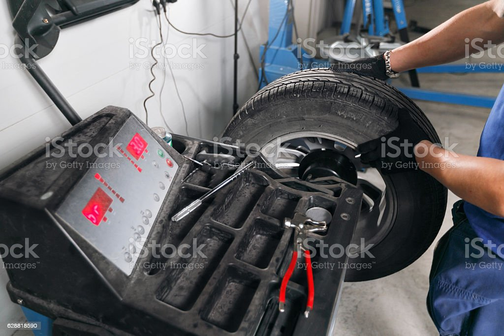 wheel balancing. Mechanic removes car tire closeup. Machine for removing stock photo