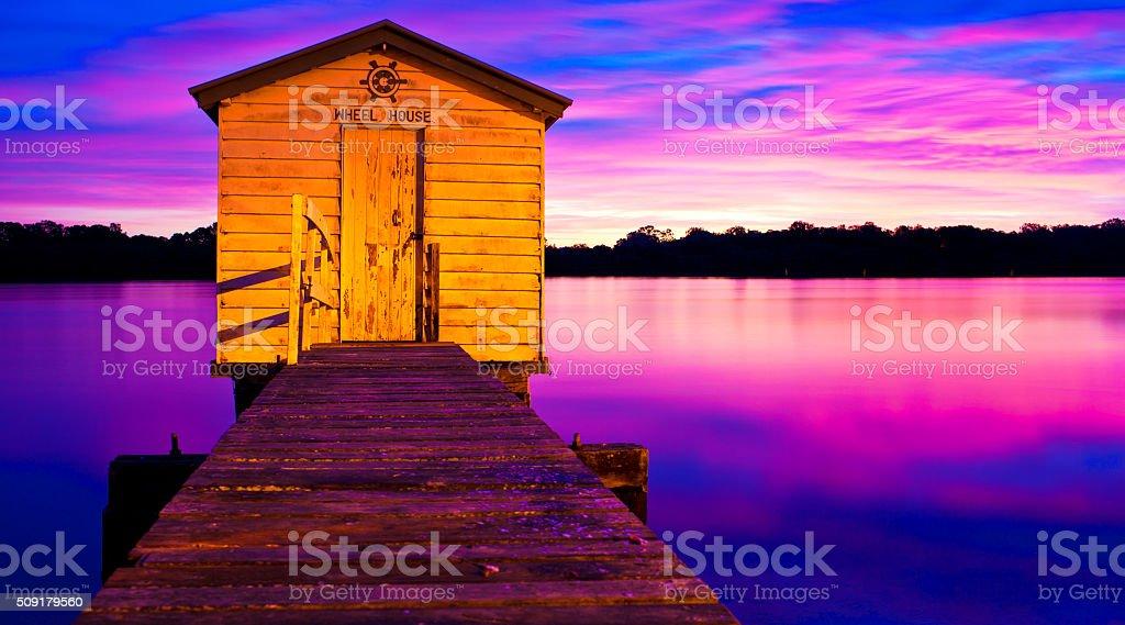 'Wheel House' jetty shack on river at sunrise stock photo