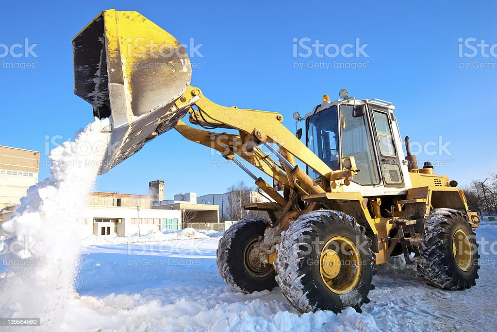 Wheel loader machine unloading snow stock photo