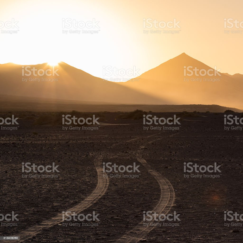 Wheel tracks in sand and dramatic landscape. stock photo